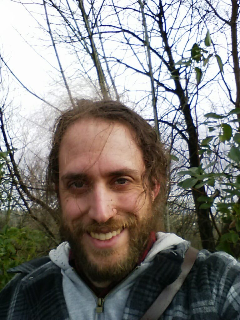 An image of the author smiling, with bare trees and a few leafy shrubs in the background. Wind is tugging his hair into fly-aways, and it is raining around him despite the bright grey sky.