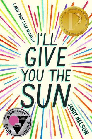 The cover to the book I'll Give You The Sun. The title text is written out in the center, with bright multicolored lines shooting out from it in all directions, like a starburst.