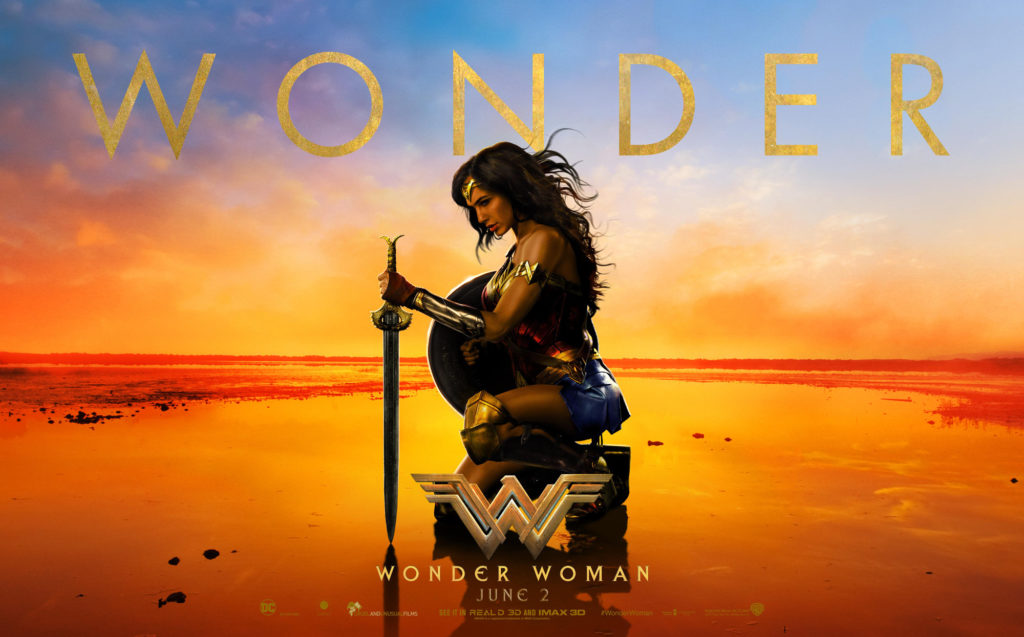 An image of Gal Gadot as wonder woman, kneeling on a beach at sunset. Her sword is planted in the ground in front of her, her left hand on the hilt. She holds her shield in her right hand. She is wearing her full armor, and her hair is teased lightly in the breeze. Her head is slightly bowed, as if in contemplation.