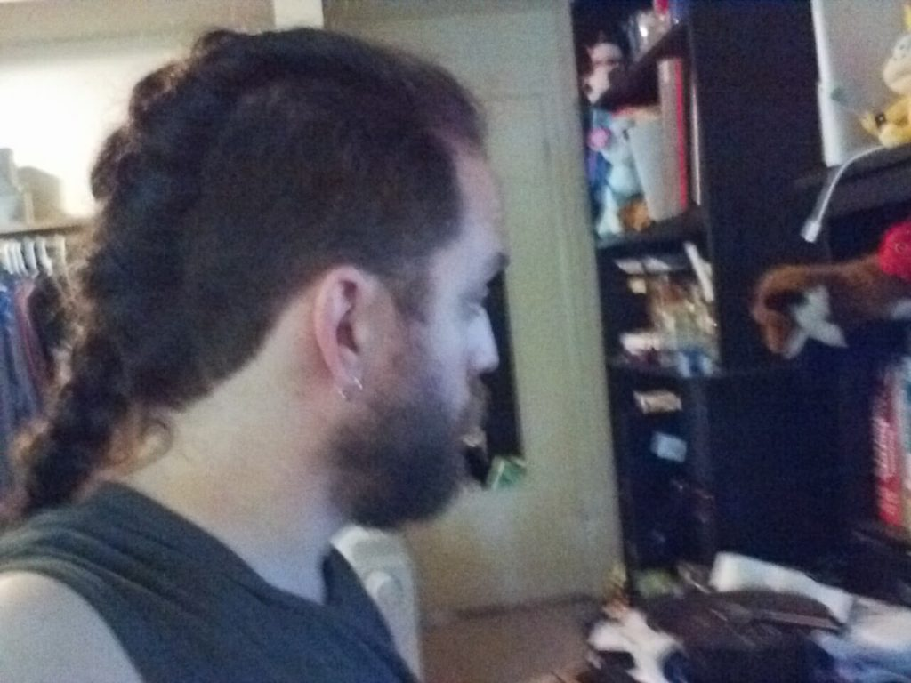 Ian facing to the right,showing his long hair braided along his mohawk line.