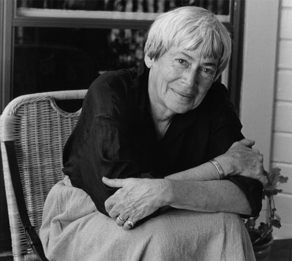 Le Guin sitting in a woven chair, arms crossed while leaning forward and smiling at the camera.