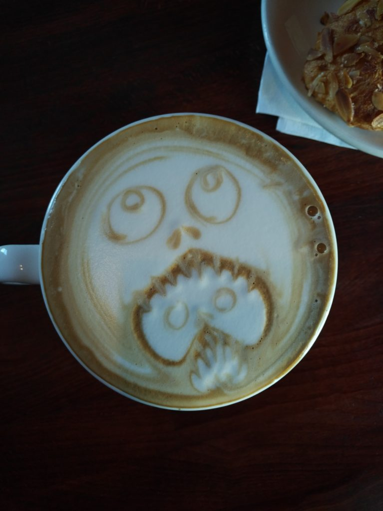 A cup of coffee with latte art depicting, as far as I can tell, a head eating another head with its fangs.