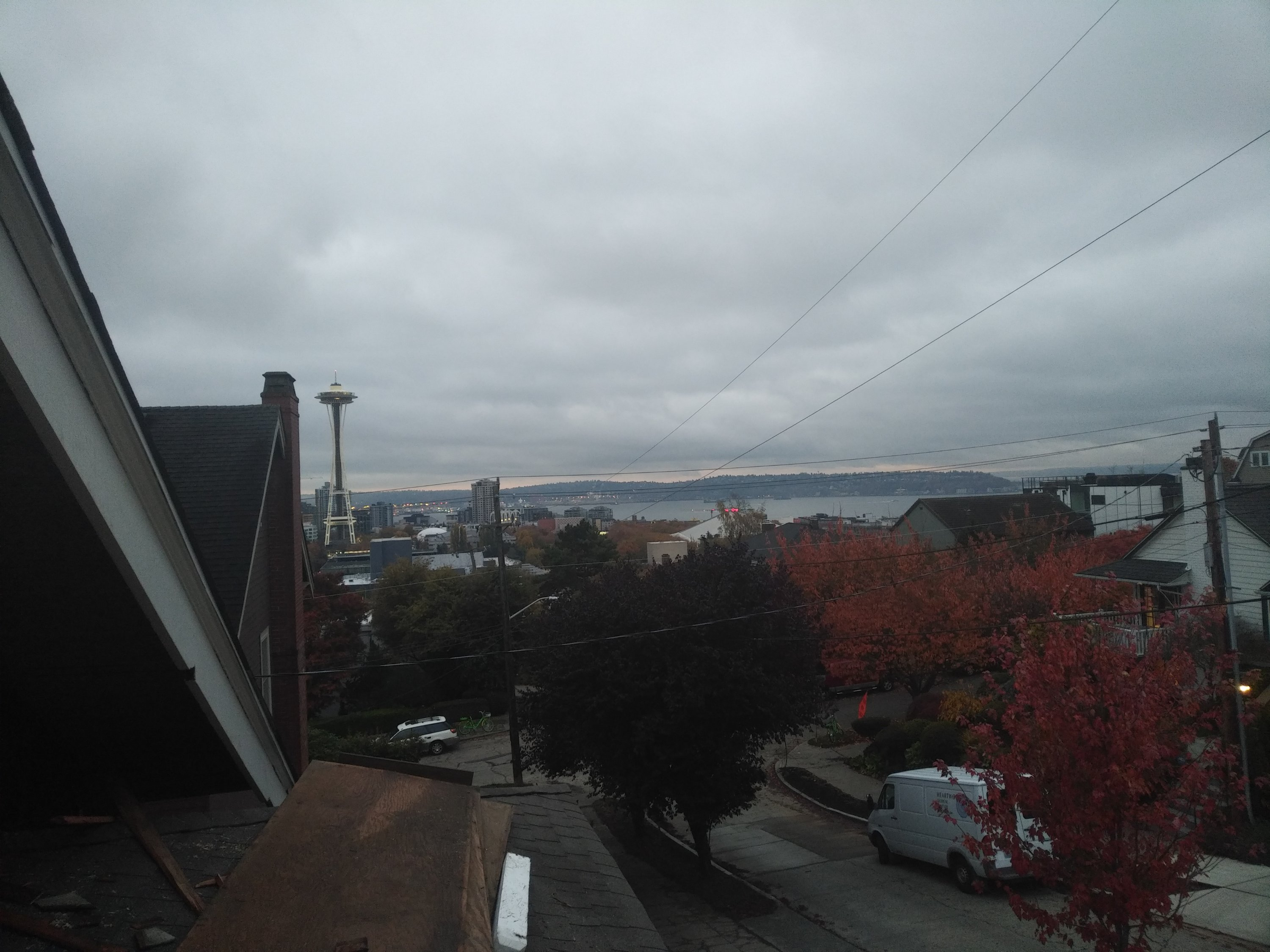A view from a house rooftop overlooking Seattle. The space needle, the sound, and several large buildings are visible. The sky is covered by grey rainclouds.