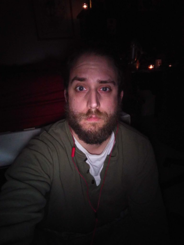 The author squinting slightly at the camera and looking tired while in a dark room.