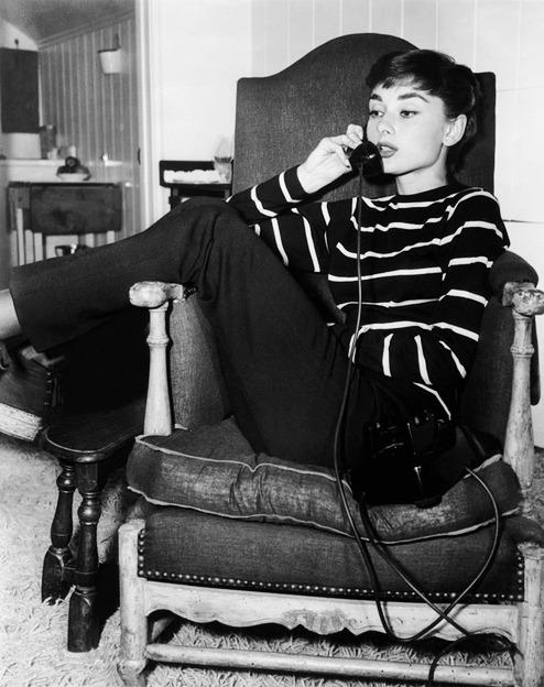 Audrey Hepburn sitting in a chair, talking into a landline phone.