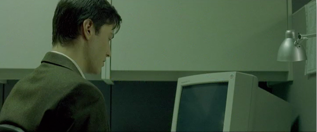 Neo from the Matrix, in an ill-fitting suit, looking at a monitor in his work cubicle.