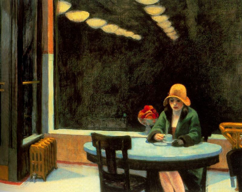 A young woman sits alone at a table, looking into her cup of coffee, in an automat. The light fixtures are reflected in the dark window, chained reflections stretching out into the night.